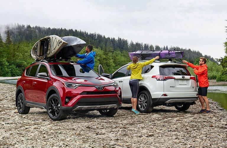 red and white 2018 toyota rav4 hybrids next to each other with mounted kayaks and young people around them