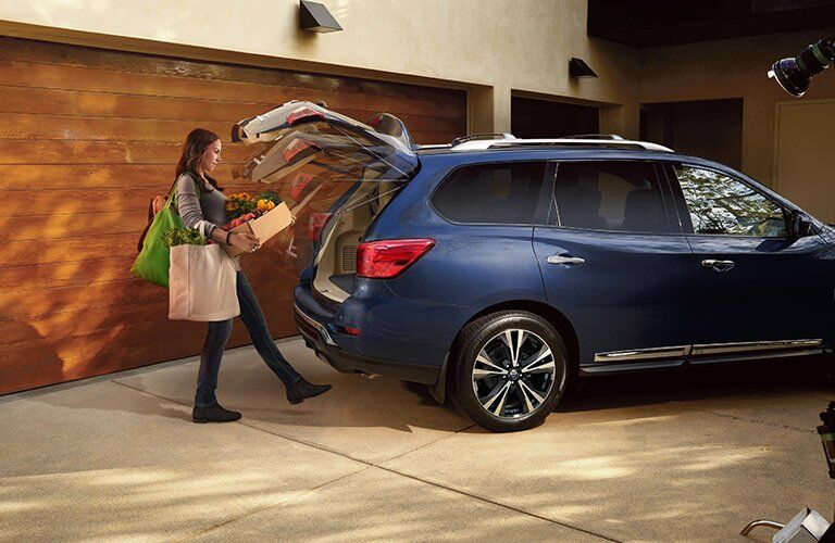Woman carry boxes opens 2017 Nissan Pathfinder liftgate with foot