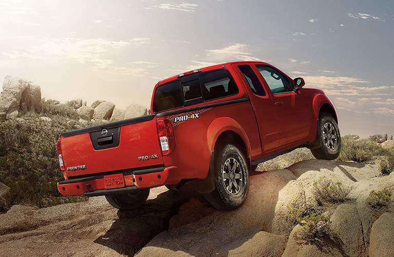 Tailgate and passenger side profile of the 2018 Nissan Frontier driving up a rocky incline