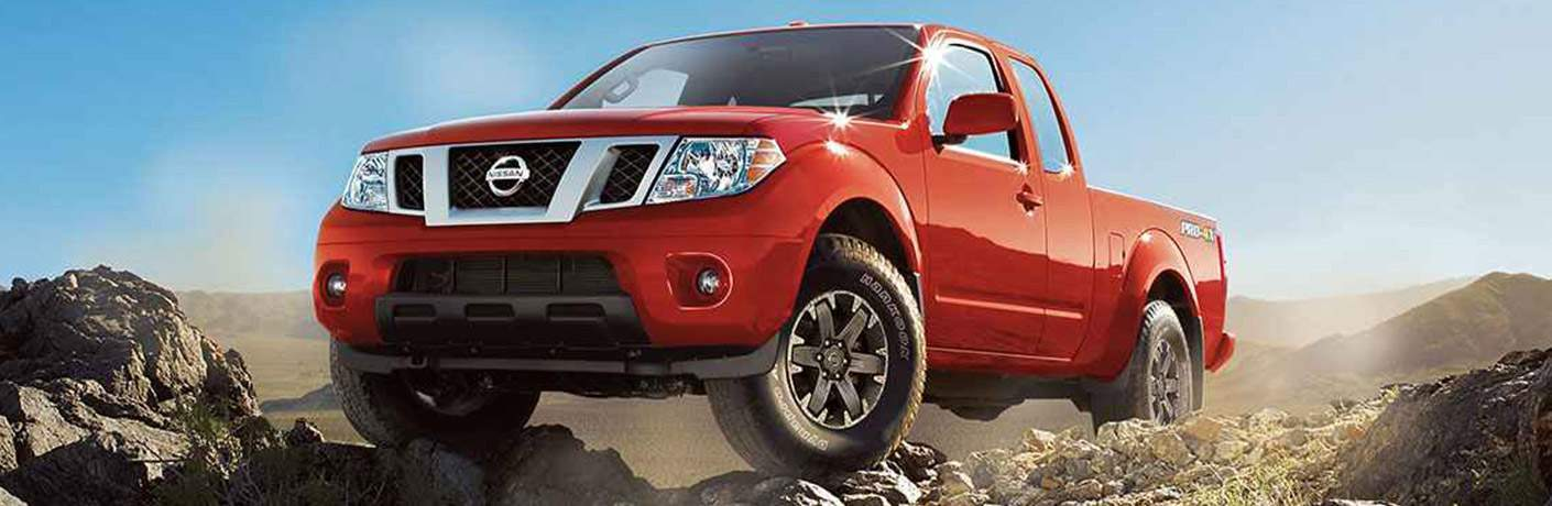 Front Grille of the 2018 Nissan Frontier driving over rocky terrain