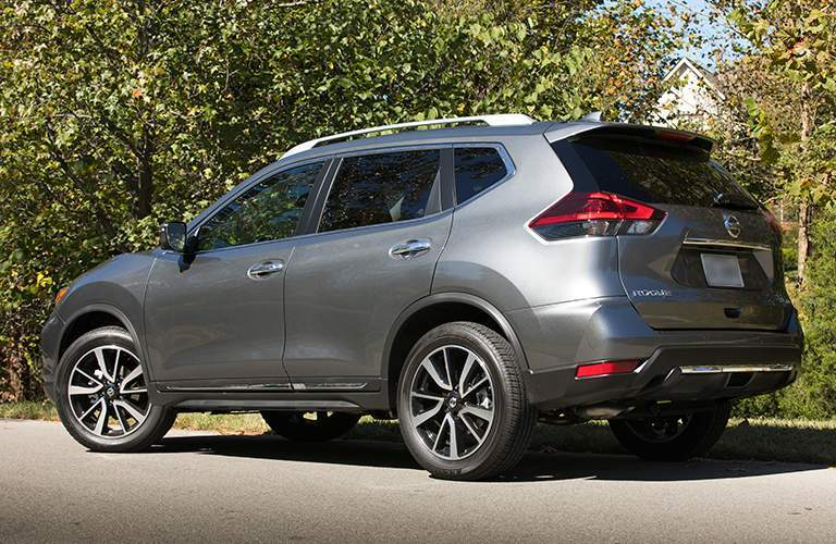 Rear three quarter profile of the 2018 Nissan Rogue parked on a street surrounded by trees with a house in the background