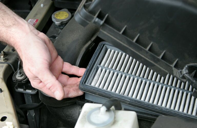 Hand holding air filter inside vehicle engine