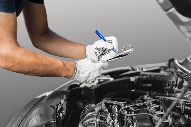 Mechanic holding clipboard to inspect vehicle engine