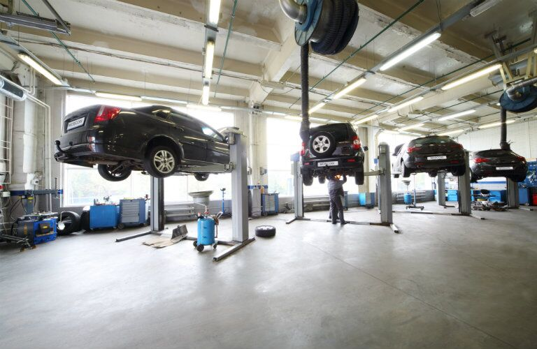 Four black vehicles lined up side by side in vehicle service bay