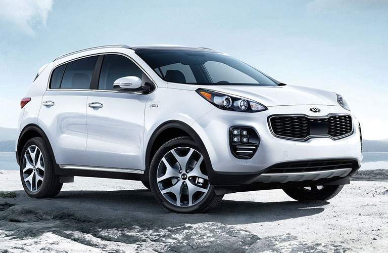 A front right quartering image of a white Kia Sportage on a white sand beach