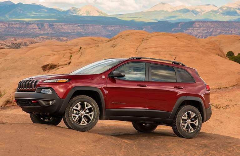 A full left profile view of a red Jeep Cherokee in the desert