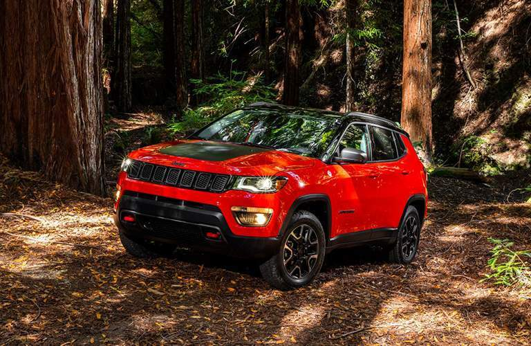 A red Jeep Compass on a trail in the woods