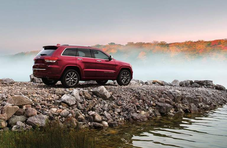 A right profile view of the Jeep Grand Cherokee on a rocky out crop