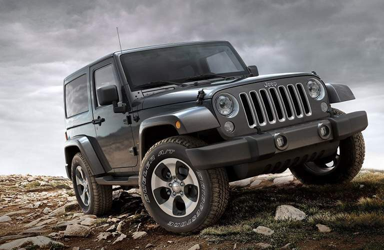 A tilted front left quarter view of a Jeep Wrangler over rock-covered ground
