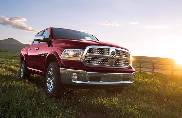 A up-angled photo of a Red Dodge Ram 1500 showing its right front quarter in a farm field