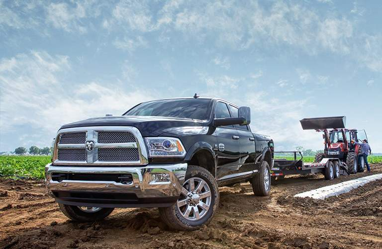 An up-angled photo of a black Ram 2500 in a muddy field unloading a front-end loader