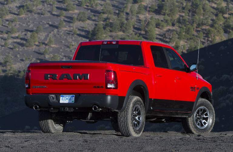 A rear quarter view of a red 2018 Ram 1500 parked on gravel