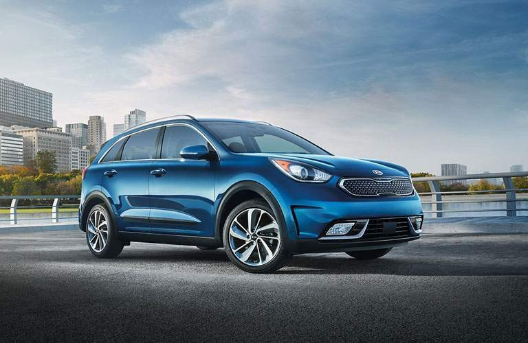 A quartering left front image of a blue Kia Niro in front of a city scape