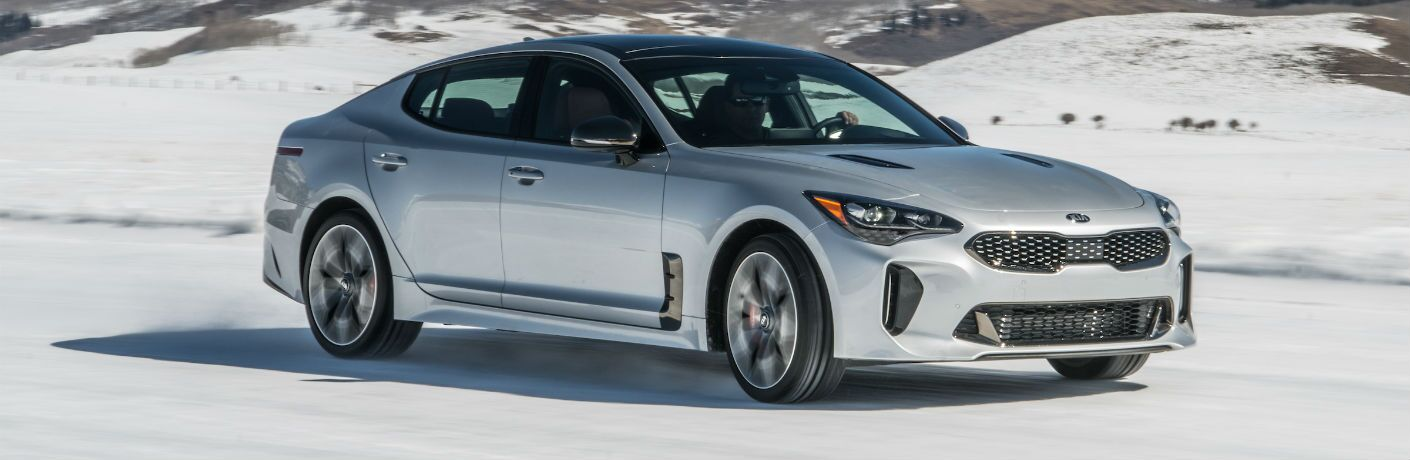 A right quartering profile photo of the 2018 Kia Stinger driving over snow.