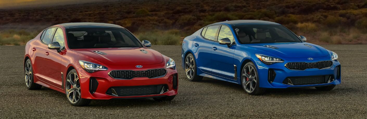 A pair of 2018 Kia Stinger models parked side-by-side in the desert.