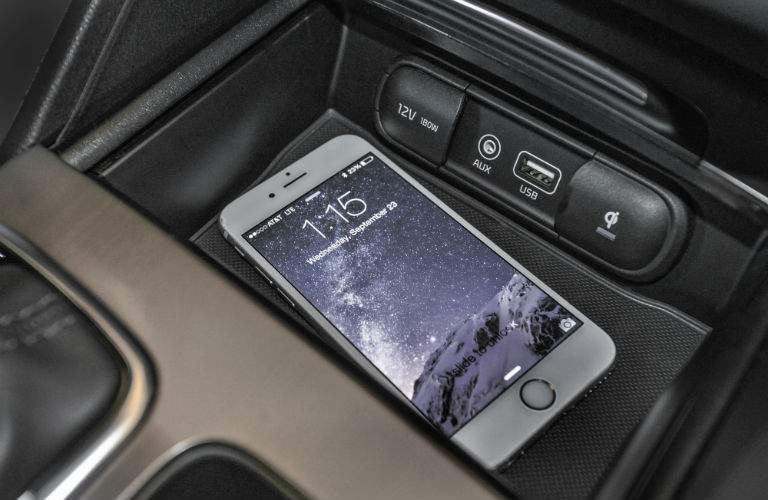A photo of a smartphone in a tray located in the front of a 2018 Optima