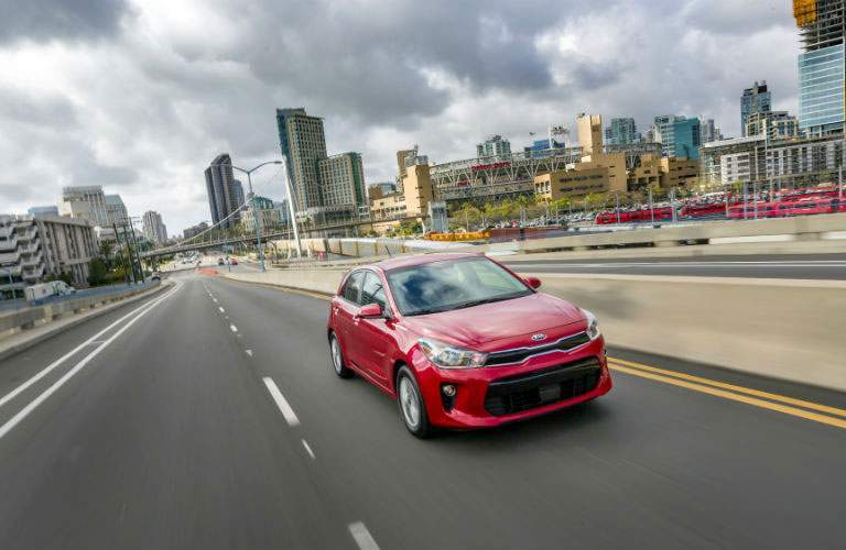 red 2018 Kia Rio5 driving down expressway with cityscape in background