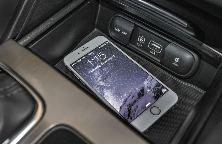 A close up photo of a smartphone sitting in a tray inside of the 2018 Optima.