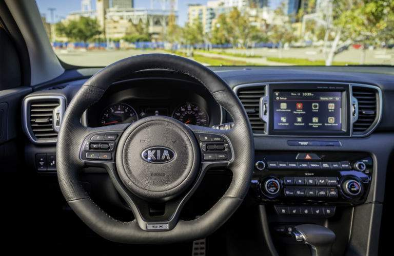 An interior photo of the driver's cockpit and infotainment system found in the 2018 Sportage.
