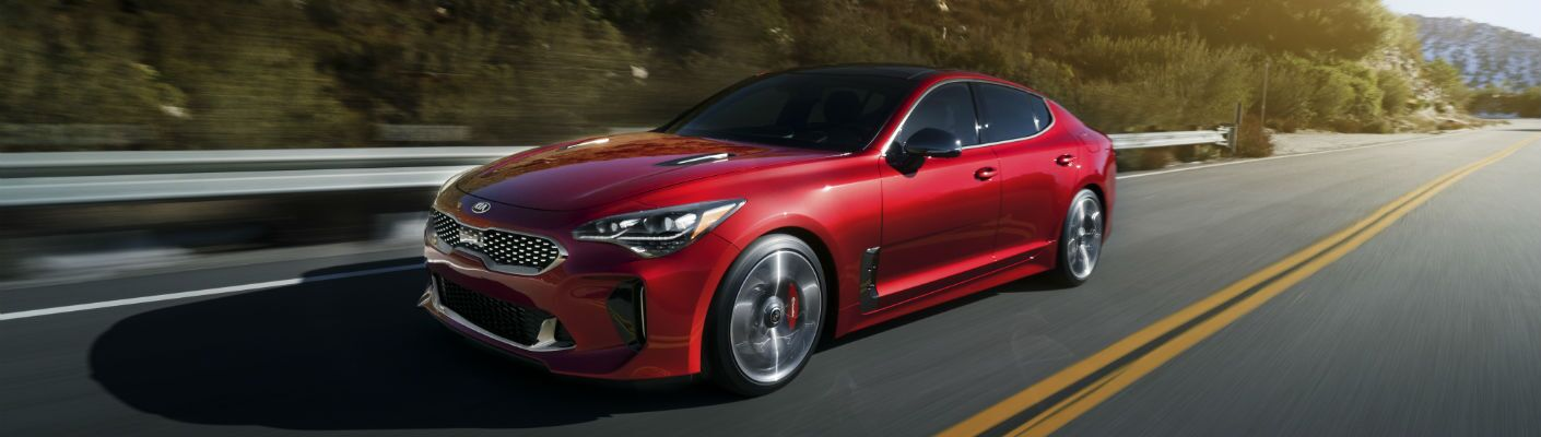 A left front quarter photo of the 2018 Kia Stinger GT in motion on the road.