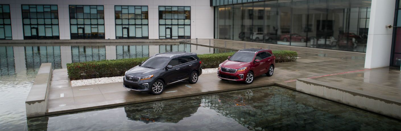 A photo of two 2019 Kia Sorento models parked by a water feature.