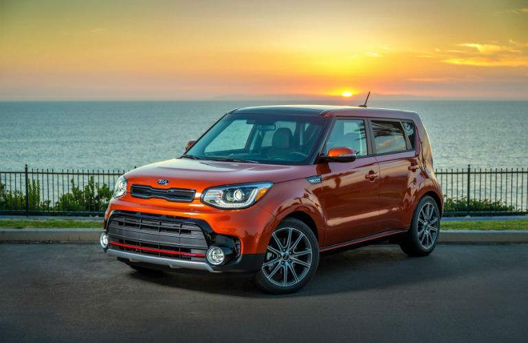 A left front quarter view of an orange 2018 Kia Soul parked in front of the ocean