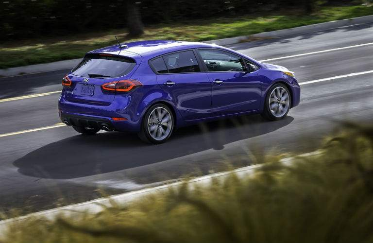 A right profile view of a blue 2018 Kia Forte hatchback model on the road
