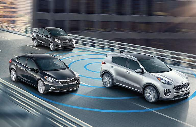 A photo illustration of a 2018 Kia Sportage showing off its active safety features like blind spot monitoring