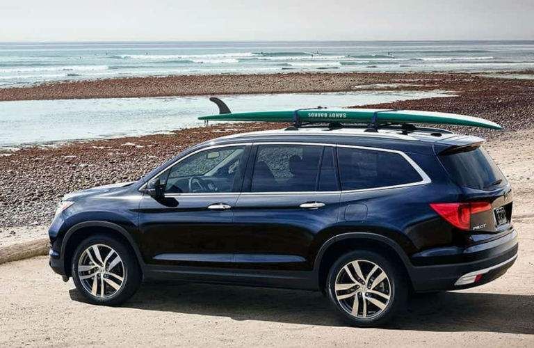 2018 Honda Pilot with a surfboard on top of it