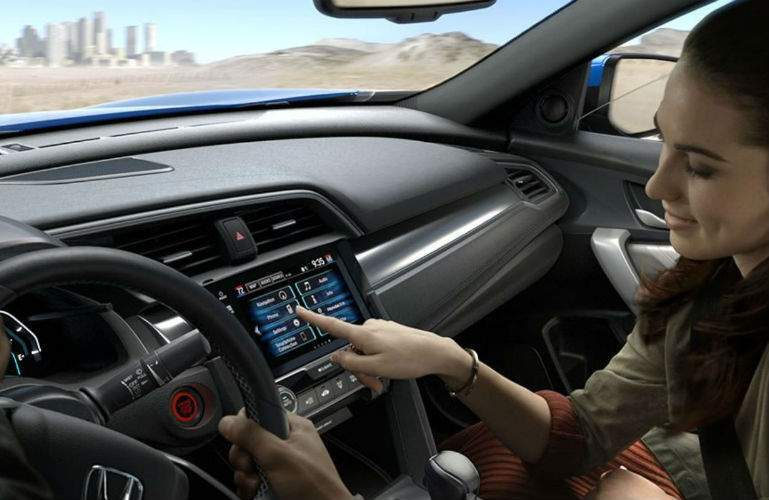 Woman using infotainment system in 2018 Honda Civic Coupe