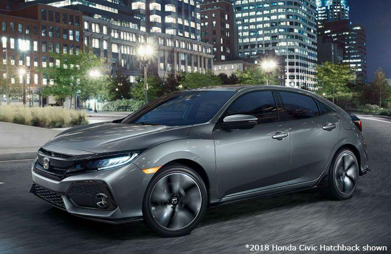 2018 Honda Civic Hatchback driving around a city at night