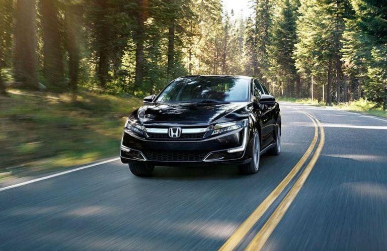 2018 Honda Clarity Plug-in Hybrid driving towards the camera through a woods