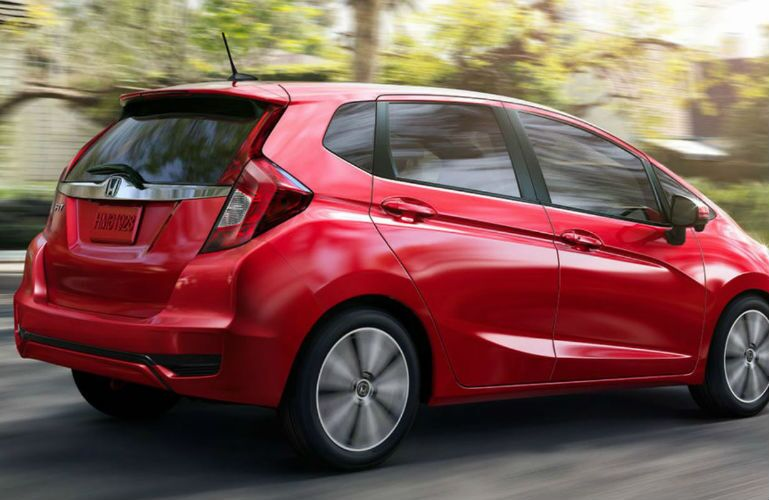 2019 Honda Fit in Milano Red driving fast in a neighborhood