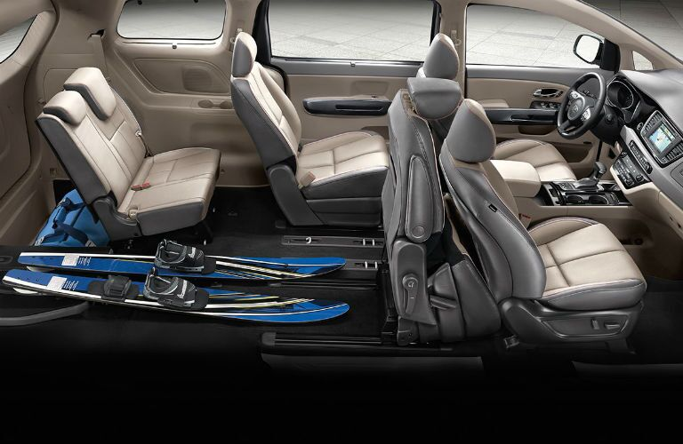 side aerial view of interior seats of 2018 kia sedona with seats folded for skis