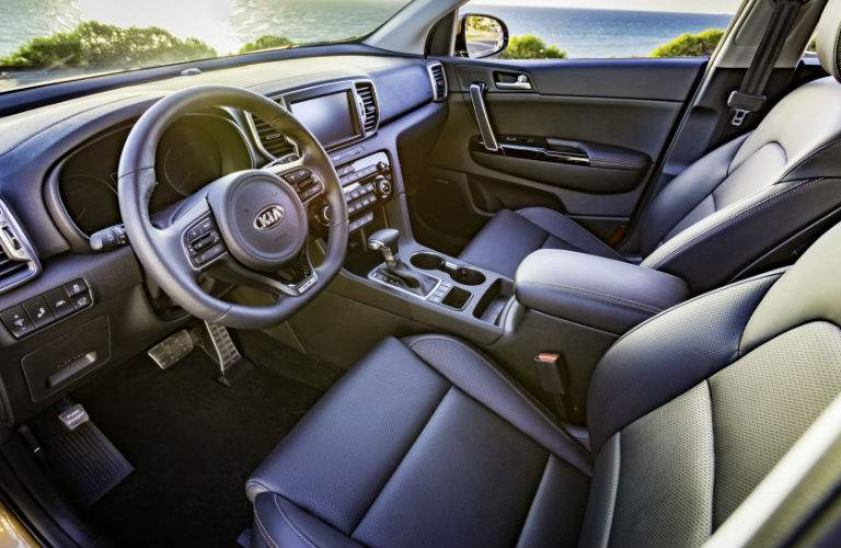 side view of front interior cabin of 2018 kia sportage including seats, steering wheel, and center console