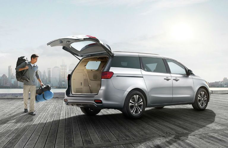 2019 Kia Sedona with man loading luggage into cargo area