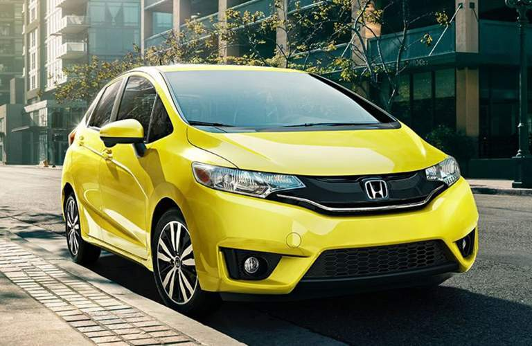 2017 Honda Fit bright yellow parked on city street in urban tile environment