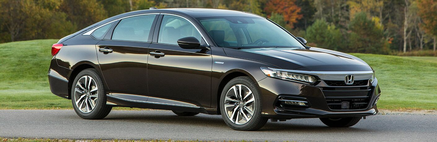 2018 Honda Accord Hybrid exterior shot with black paint job parked on an asphalt road open clearing in front of a fall forest