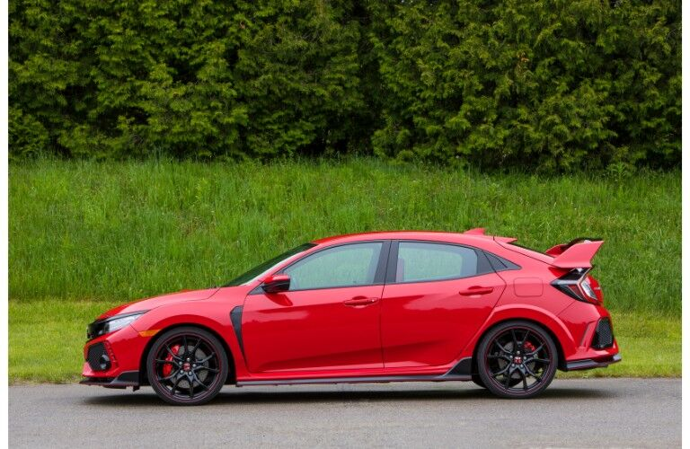 2018 Honda Civic Type R exterior side shot red paint coat parked on a road next to a greenery forest