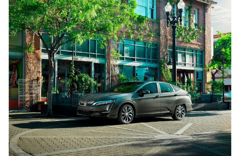 2018 Honda Clarity Electric exterior shot with gray green paint color parked on a tiled plaza outside a brick building