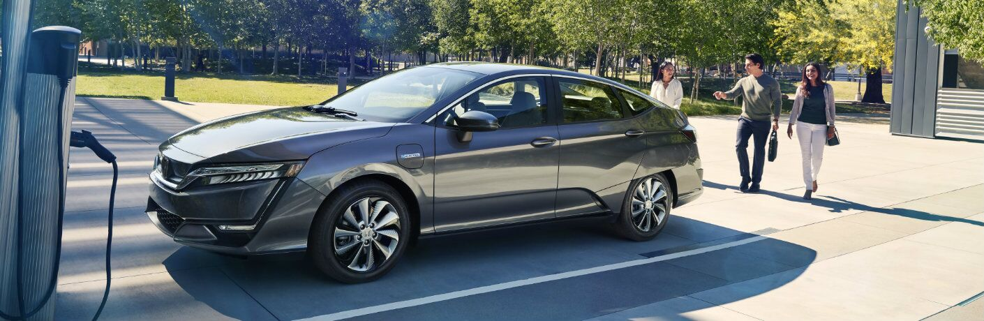 2018 Honda Clarity Electric exterior side shot with gray metallic paint color parked outside an electric charging station near a forest as its driver and friends approach