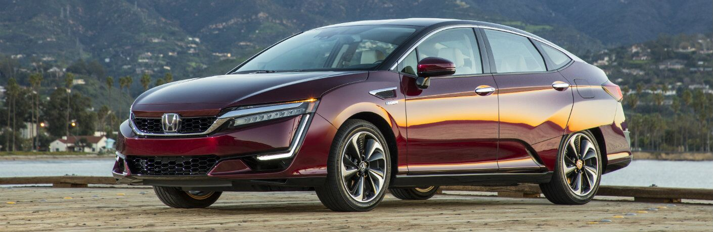 2018 Honda Clarity Fuel Cell exterior shot with red maroon paint color parked at a wooden piere next to a lake and mountains