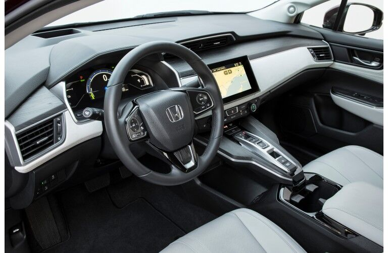 2018 Honda Clarity Fuel Cell interior shot of front seating upholstery, dashboard technology, and steering wheel with Honda badge