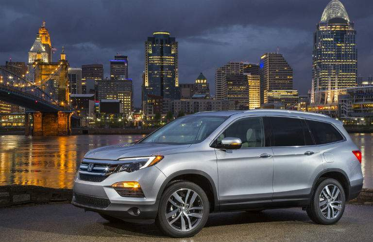 2018 honda pilot elite in silver shown from exterior in front of nyc skyline front 3/4 view