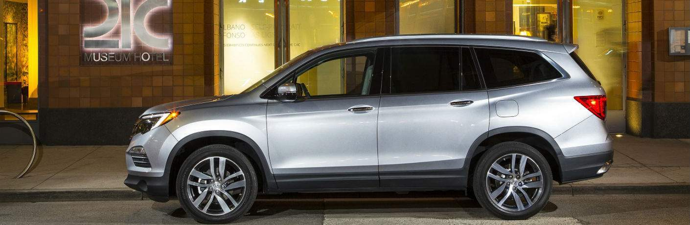 2018 Honda Pilot Elite in Silver parked outside of fancy hotel profile view with wheels shown
