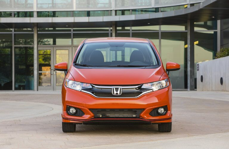 2019 Honda Fit exterior shot orange paint of front grille, headlights, and fascia parked in front of a building