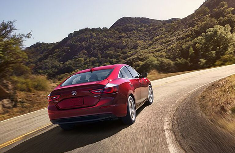 2019 Honda Insight exterior rear shot with red paint color driving up a curving road near grassy mountains