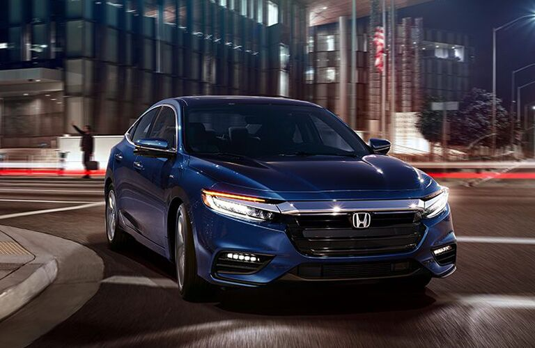 2019 Honda Insight exterior front shot with blue paint color driving through a city a night