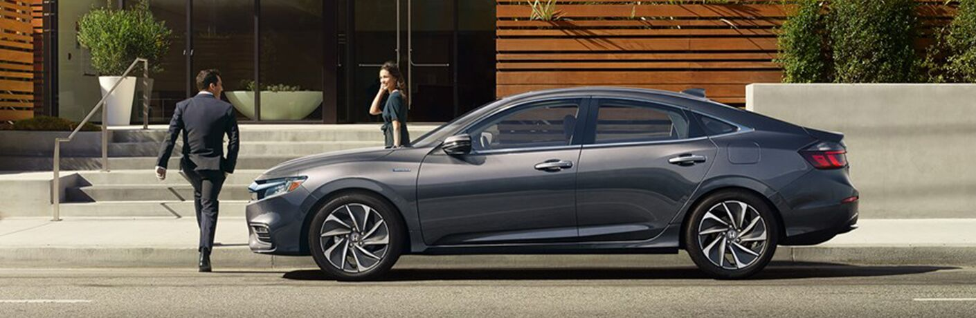 2019 Honda Insight exterior side shot parked next to a building as driver and passenger exit to the stairs