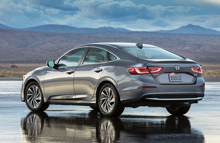 2019 Honda Insight exterior rear shot parked on a wet concrete lot with mountains in the background
